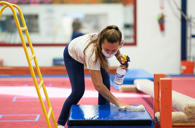 Coach disinfecting equipment after gymnastics class