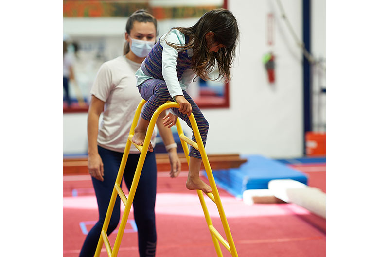 Coach practices COVID safety with girl on a ladder