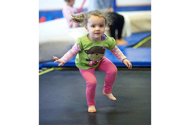 Girl bouncing on the trampoline at Preschool Gymnastics