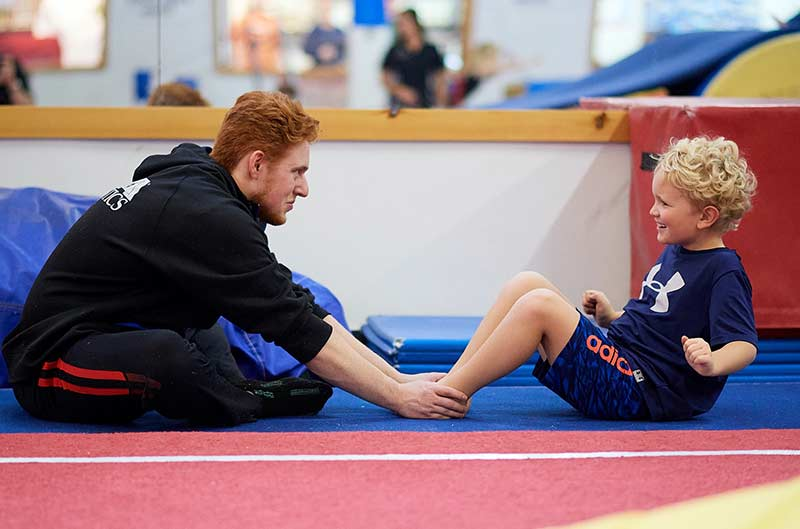 Boy doing situps with coach during gymnastics classes