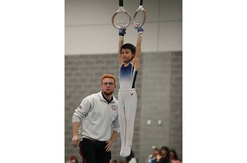 Boys Competitive Team coach looking on while athlete competes on still rings