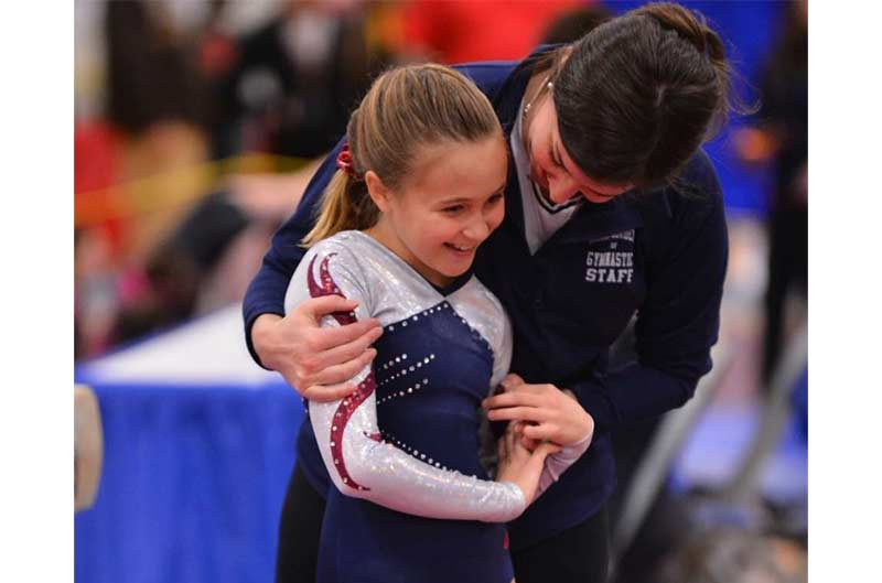 Girls Competitive Gymnastics coach congratulating athlete after routine