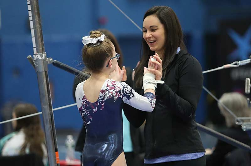 Girls Competitive Gymnastics coach congratulating athlete after uneven bars routine