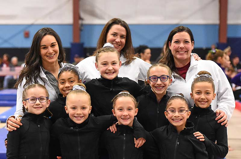 Girls Competitive Gymnastics team with coaches