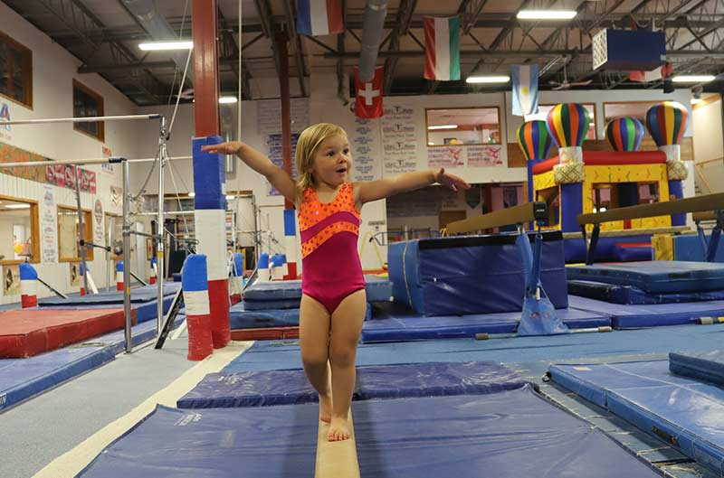 Preschool girl on a balance beam