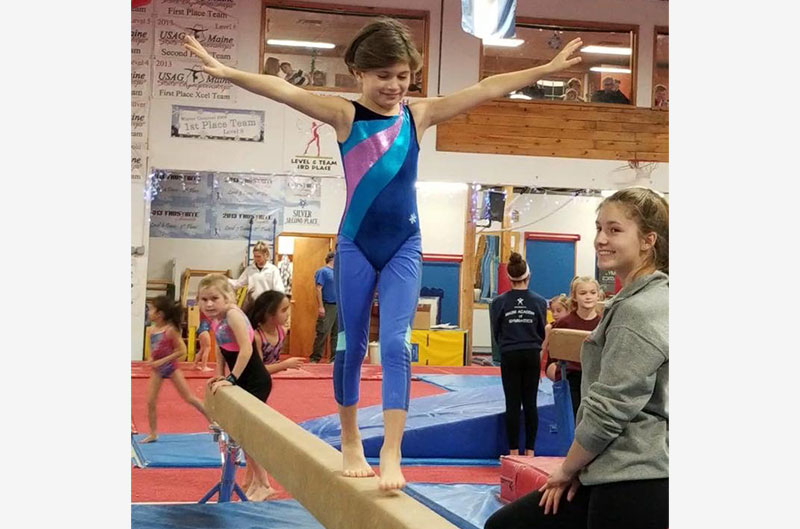 Pre-team girl practicing on balance beam