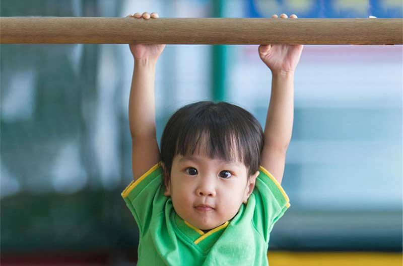 Preschool boy hanging from high bar