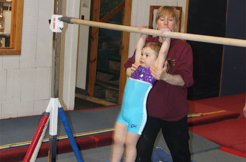 Gymnastics coach assists student on high bar
