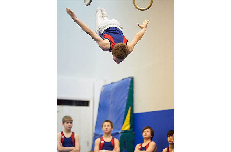 Gymnastics boy dismounting from rings