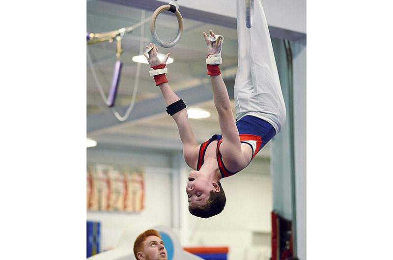Gymnastics coach spotting boy's dismount from rings