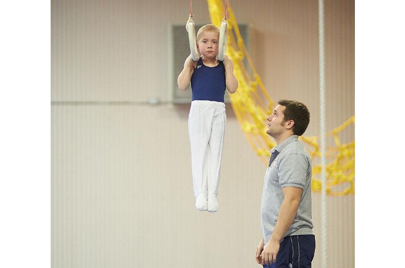 Coach spotting competitive gymnast on rings
