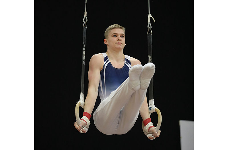 Gymnast holding an 'L' on rings