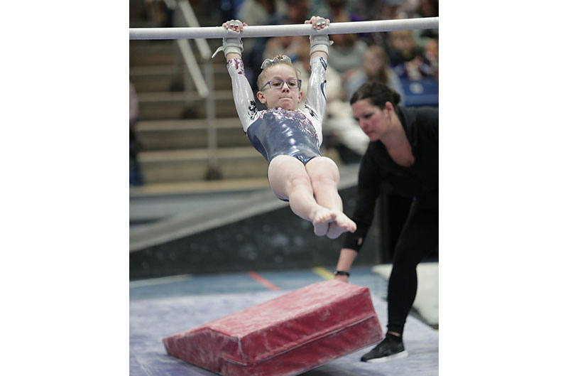 Girl competing on uneven bars