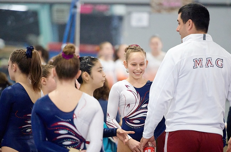 Gymnastics coach congratulating girls