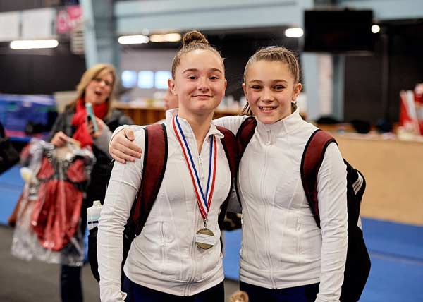 Two competitive gymnastics girls, one with a medal
